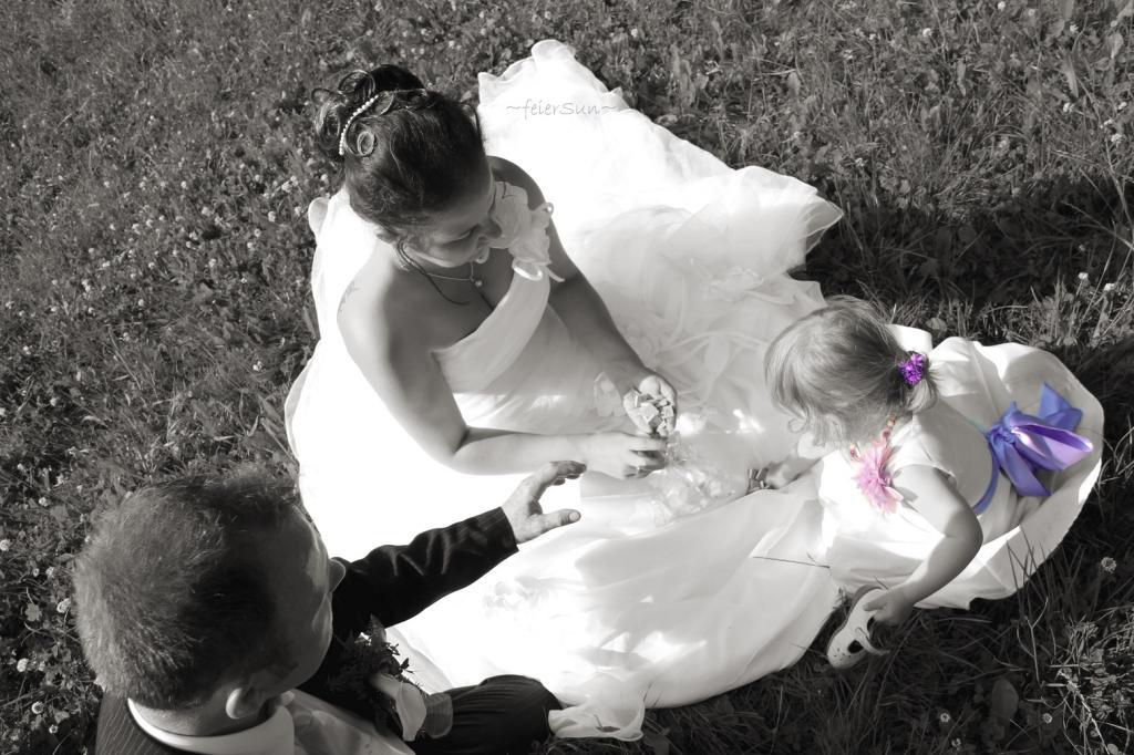 Paar mit Kind sitzt auf einer Wise und legt Buchstaben zusammen. Frau Trägt Hochzeitskleid und Mann Anzug. Das Kind ein weißes kleid mit lilafarbener Schleife.