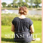 """Eine Frau sitzt mit dem Rücken zur Kamera und schaut auf die Elbe. Sie trägt einen blauen Anzug und schaut in die Ferne mit der Aufschrift """"das Gefühl nicht komplett zu sein - Sehnsucht - www.ferierSun.de!"""