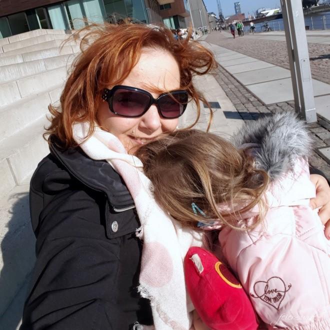 Mutter hält Tochter im Arm und Tochter kuschelt sich an sie an.
