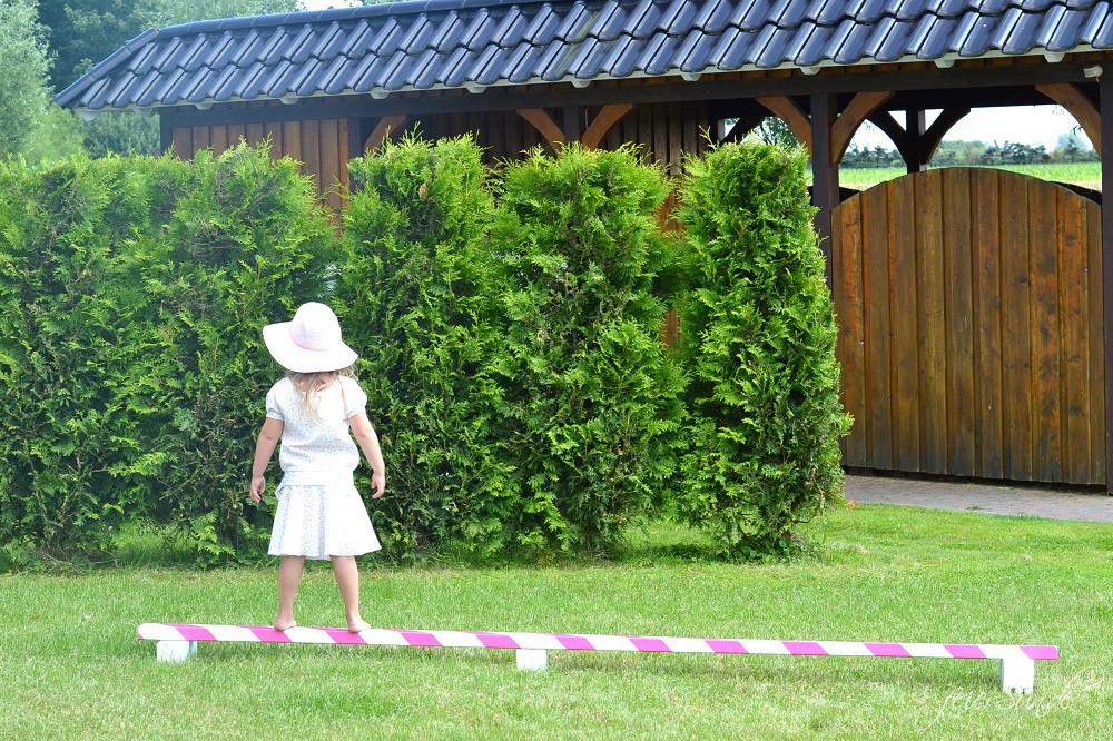 Mädchen steht auf ihrem Balancierbalken im Garten. Er ist weiß und pink gestreift und sie trägt dabei ein weißes Kleid und einen Sonnenhut.