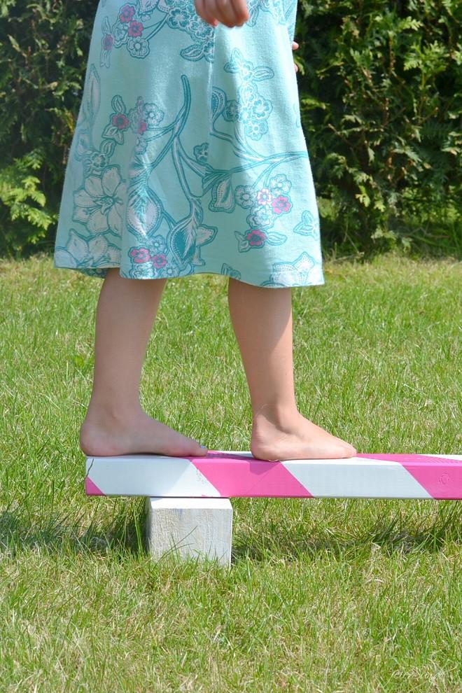 Mädchen balanciert auf ihrem Balancierbalken im Garten und trägt ein blaues Kleid dabei.