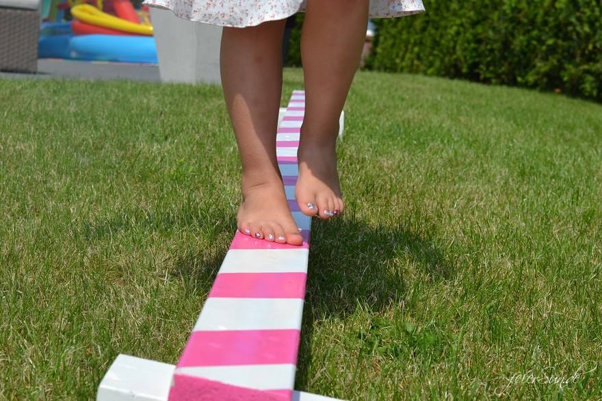 Ein Mädchen balanciert auf ihrem Balancierbalken im Garten.