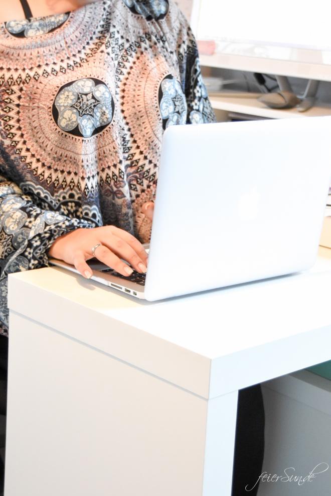 Frau arbeitet am Macbook. Sie ist Unternehmerin.