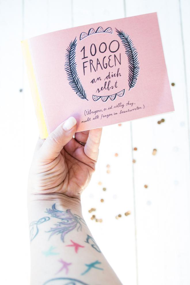 Hand mit Tattoos hält das Büchlein 1000 Fragen an dich selbst aus dem Flow-Magazin. Im Hintergrund goldenes Konfetti.