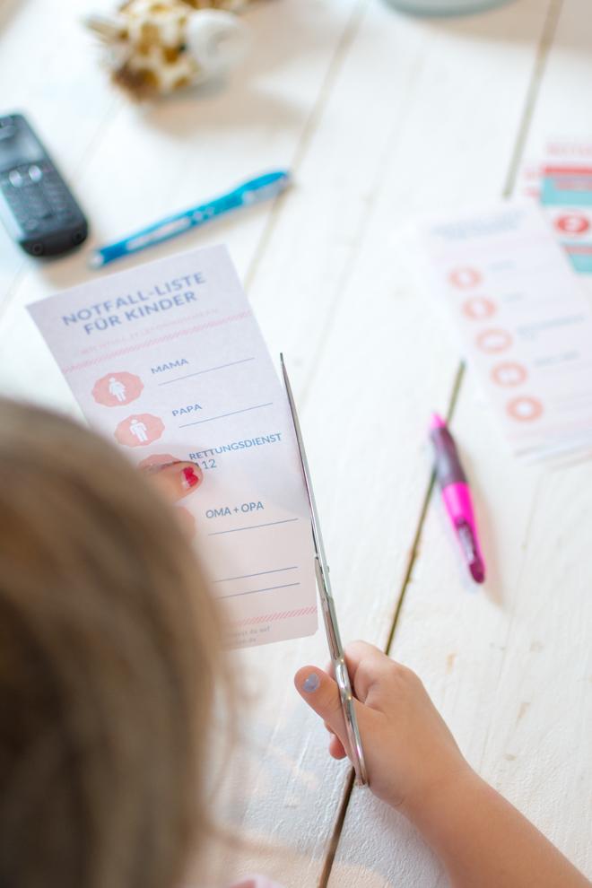 Kind bastelt sich eine Notall-Liste mit den wichtigsten Telefonnummern und scheidet die Liste aus. Diese Liste gibt es als Design-Freebie auf dem Blog feierSun.de