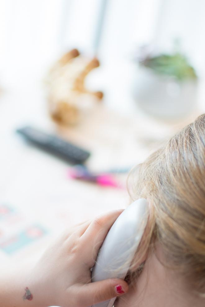 Mädchen mit Nagellack und Klebetattoo telefoniert mit der Rettungsstelle um sich Hilfe zu holen.
