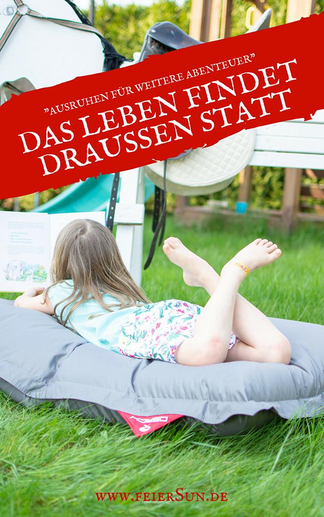 """Mädchen liegt auf einem grauen Sitzsack von QSacks und liest ein Buch über Pferde und Fohlen. Auf dem Bild steht folgende Schrift """"Ausruhen für weiter Abenteuer. Das Leben findet draußen statt - www.feiersun.de"""""""