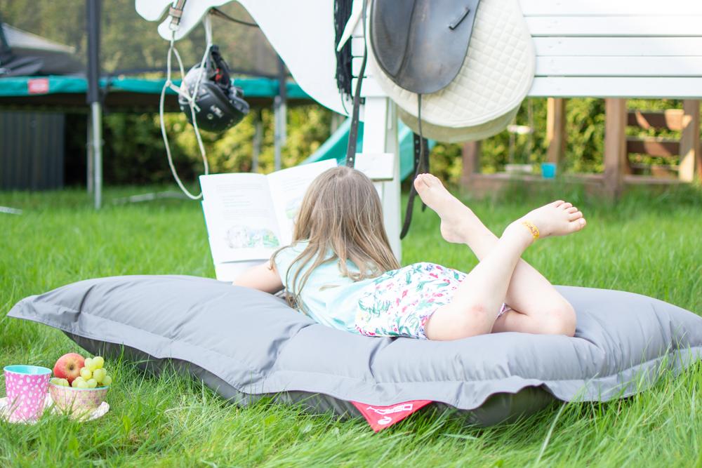 """Mädchen liegt auf einem grauen Sitzsack von QSacks und liest ein Buch über Pferde und Fohlen. Auf dem Bild steht folgende Schrift """"www.feiersun.de, Pause, Abenteuer und zwischen 2 Abenteuern liegt eine Pause"""""""