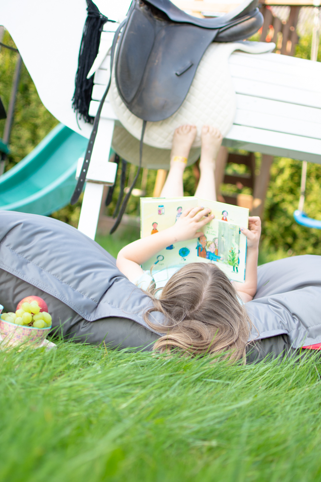Mädchen liegt auf einem grauen Sitzsack von QSacks vor ihrem Holzpferd mit den Beinen in der Luft und liest ein Buch