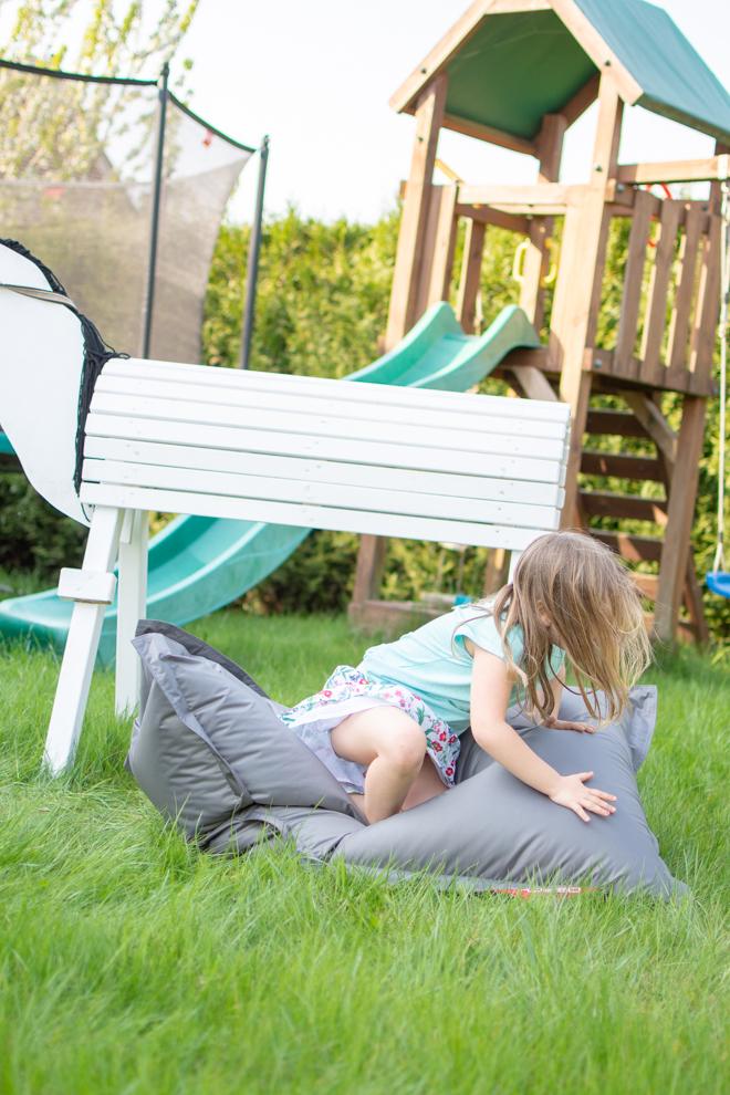 Ein Mädchen spring von ihrem weißen Holzpferd auf einen grauen Outdoorer QSack Kindersitzsack.