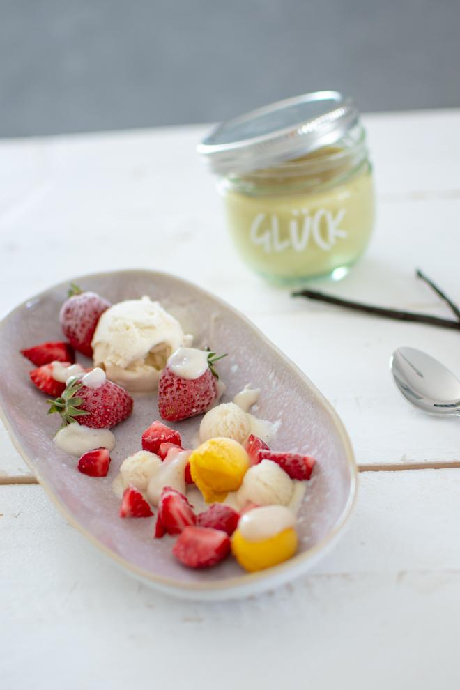 """Vegane Vanillesoße auf Sorbet mit Erdbeeren auf einem Teller angerichtet dazu kommt Kokos-Vanille-Eis und die Soße ist in einem Glücks-Glas mit der Aufschrift """"Glück"""""""