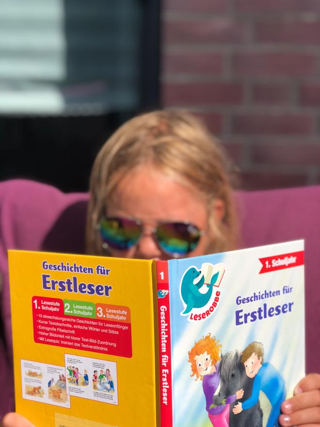 Kind liest mit einer Sonnenbrille ein Erstlesebuch. Lesen macht Spaß und das sollten wir unseren Kindern behalten. Mit dem Sommer-Lesepass macht es noch viel mehr Freude. Nicht nur in den Sommerferien.