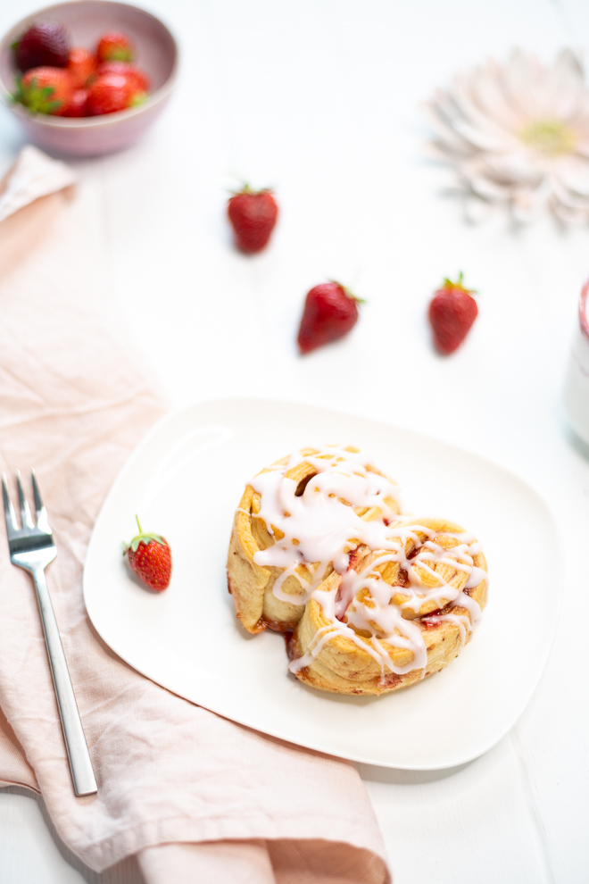 Diese Rezept für saftige Erdbeer-Schnecken mit Erdbeer-Guss sind der perfekte Sommersnack und die sommerlich, fruchtige Antwort auf klassische Zimtschnecken. #feierSun #veganbacking #veganeHefeschnecken #feierSunFood
